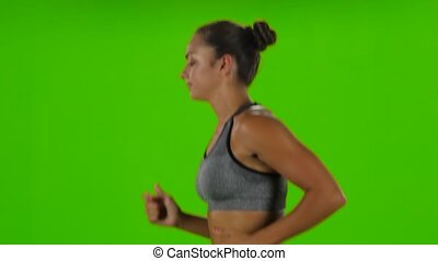 Woman running in sport clothing. Side view. Green screen -...