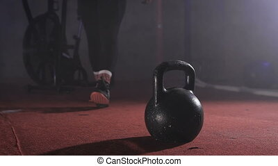 Close up of strong man in training suit going to the kettlebell and taking it with both hands and lifting it slow motion.