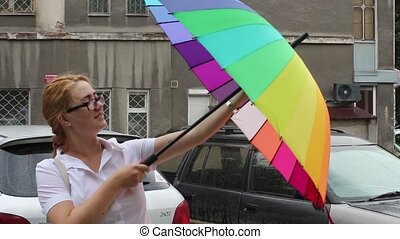 Girl trying to open an umbrella and laughs - young woman...