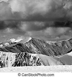 Black and white winter snow mountains in dark storm clouds....