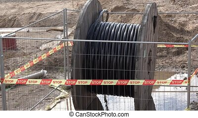 High voltage cable reel in wet dirt. Laying electricity and...