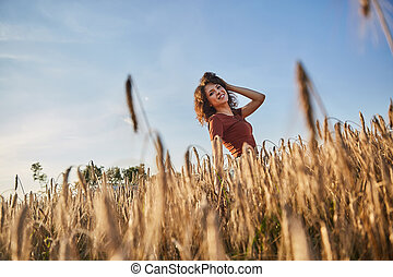 a beautiful woman standing on wheat field