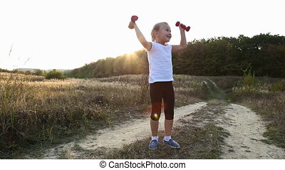 little girl podniamet dumbbells