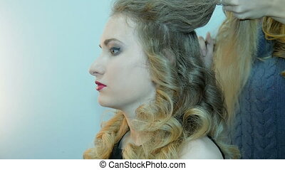 Hairdresser makes hairstyle model.