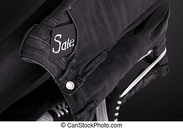 Close up of black jeans with sign Sale  hanging on clothes rack   background. Friday .