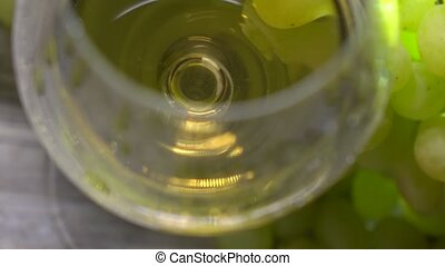 White wine glass and bunch of green grapes, top view. Winery...