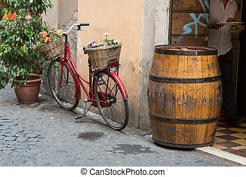 Vintage bicycle and old barrel  in front of a building