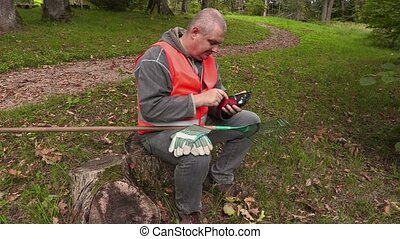 Man with rake sitting and using tablet PC