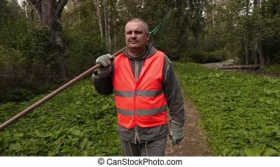 Man with rake walking in the park