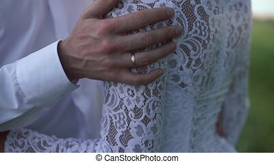 Beautiful loving couple standing on the riverside on their wedding day. Close-up.