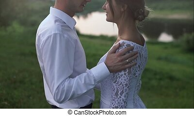 Beautiful loving couple standing on the riverside on their wedding day.