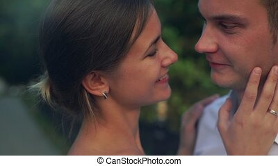 Young cheerful couple enjoying each other, eye contact, kissing