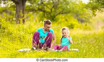 Mother with daughter sit on nature