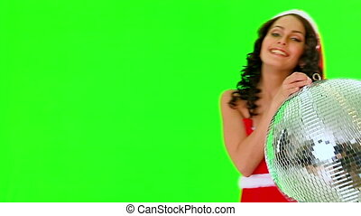Woman in Santa dress keep disco ball. Green background. Used...