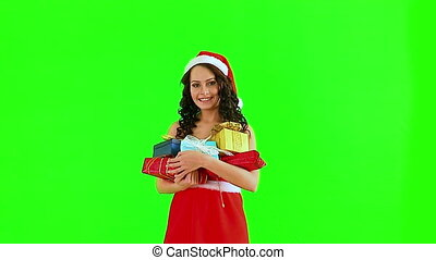 Woman in Santa hat holding gift box. Green background. -...