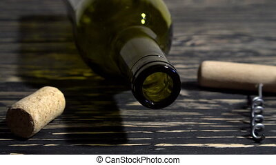 Corkscrew, cork, bottle and glass of red wine on a wooden...