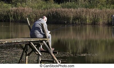 Man sitting on footbridge and fishing