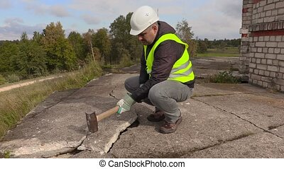 Worker with sledgehammer beats concrete