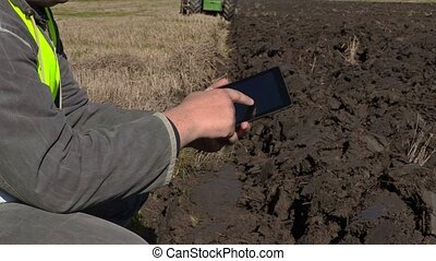 Farmer with tablet PC near moving tractor on field