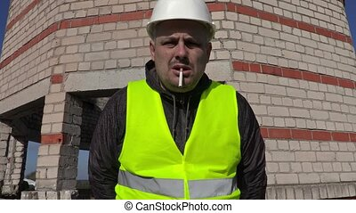 Worker with cigarette in mouth look to camera and touching...