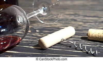 Corkscrew, cork, bottle and glass of red wine on a wooden table