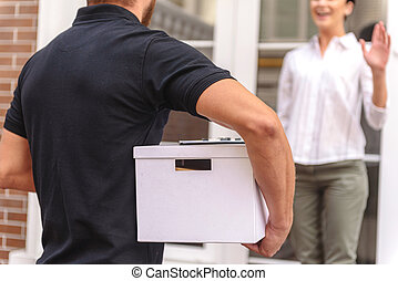 courrier delivering a box to the happy woman - happy woman...
