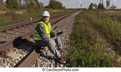 Railroad worker on the rails using tablet