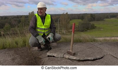 Angry worker talking near broken concrete slabs