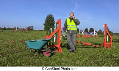 Horse handler with wheelbarrow and smart phone