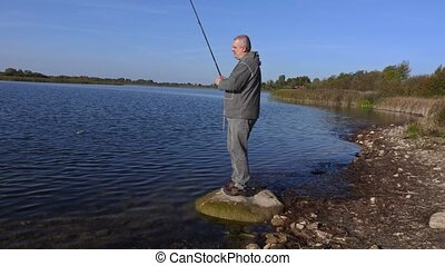 Angler on the stone near the lake checking the fishing rod