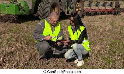 Farmers talking and writing near tractor wich plowing field