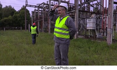 Tired electrician put helmet on head and walking away