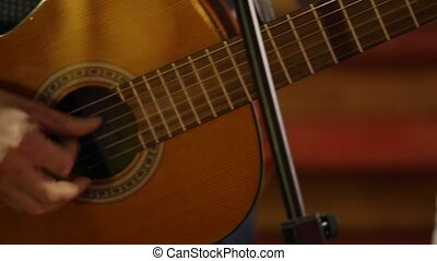 Adult man playing an acoustic guitar. The camera moves along...
