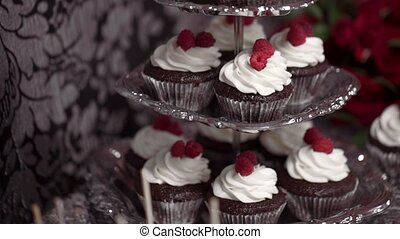 Chocolate cupcakes with whipped cream and raspberry lie on a candy bar