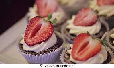 Muffins with strawberry lie on Candy Bar, close-up