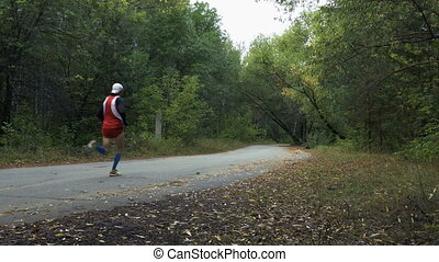 male marathon runner running on road in autumn Park with...