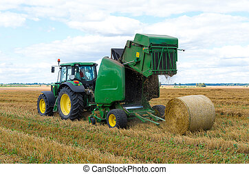 A round baler discharges a fresh wheat bale during...