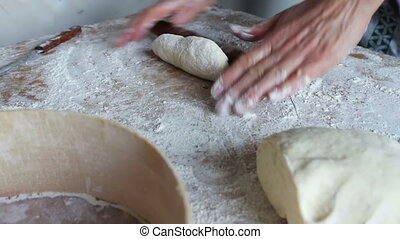 Women's hands knead the dough on a home kitchen.