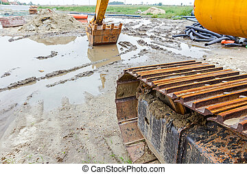 Rusted excavator bucket is parked in water at building site...