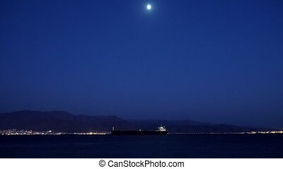 Sea shore with the ship and the moon at night
