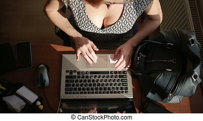 Busty sexy business woman working for a laptop. top view -...