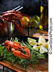 Boiled crayfish with fresh greens and a citrus on black...