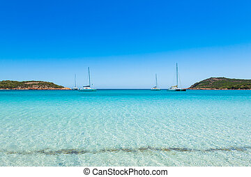 Boats mooring in the turquoise water of Rondinara beach in...