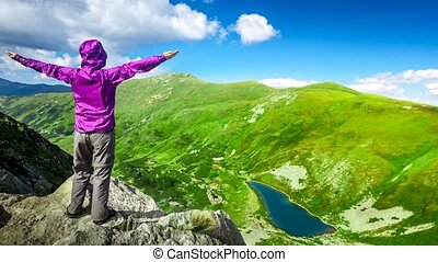 Woman on top of a mountain. 4k, 25fps - Woman standing on...