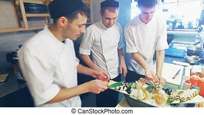 Decoration of sushi set. - Three professional chefs prepare...