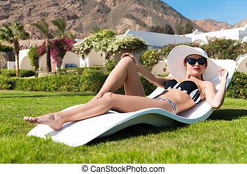 Beautiful sexy woman near pool wearing striped bikini...
