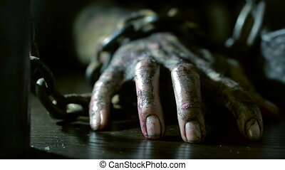 terrible burnt hand is chained to an iron chain. monster...