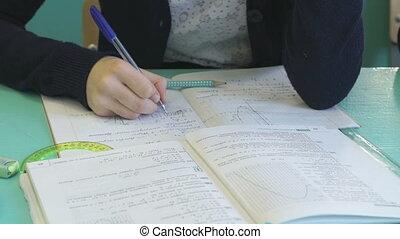 Schoolgirl writes in her copybook at the lesson - Schoolgirl...