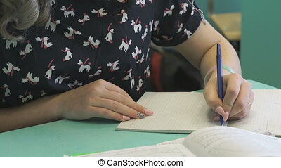 Student writes in her copybook at the lesson