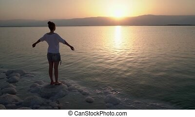 Girl looks at the sunrise over the Dead Sea - Young woman...